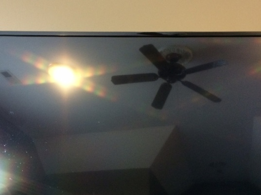 A fan of light, beside the image of an actual fan, in a television screen.