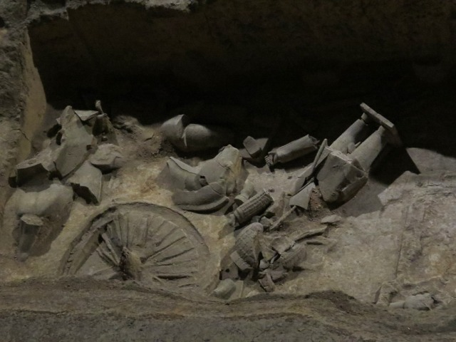 Fragments of horses, warriors, and a chariot wheel.
