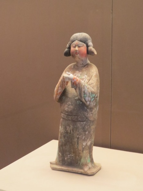 Painted figure of a standing female attendant.